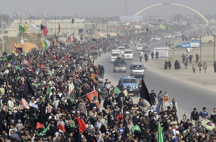 Shi'ite pilgrims hold banners and flags as they walk from Baghdad to attend the Al-Arbain solace at Kerbala