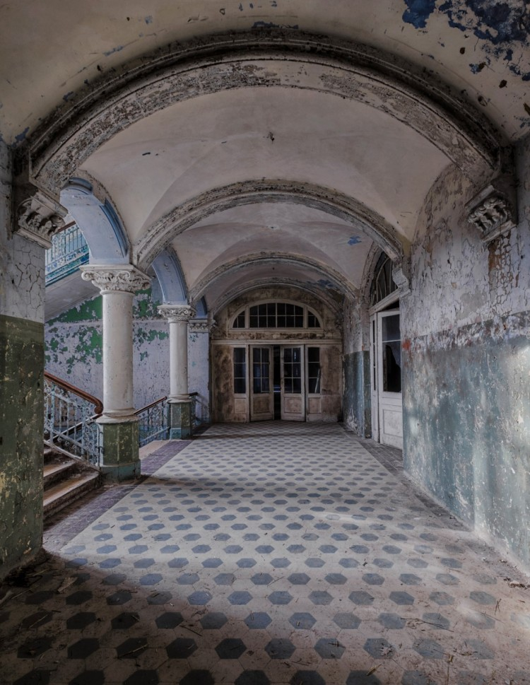 abandoned entry hall with staircase and pillars